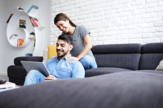 Girl Massaging Boyfriend On Sofa At Home